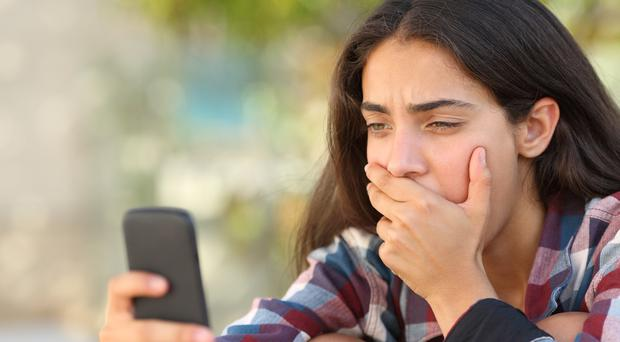 Worried teenager looking at her smart phone [File photo]