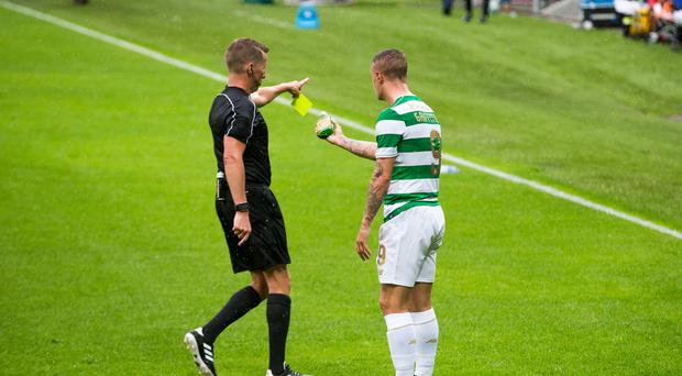 Celtic player Leigh Griffiths speaks with referee Alejandro Jose Hernandez Hernandez after a glass bottle of Buckfast was thrown at him as he attempted to take a corner kick during the UEFA Champions League Qualifying, Second Round, First Leg match at Windsor Park, Belfast. Liam McBurney/PA Wire