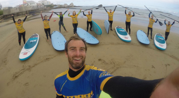 Surf's up: Carl Russell takes a selfie with some of his pupils on the strand