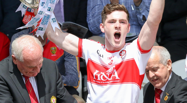 Captain fantastic: Derry skipper Padraig McGrogan raises the trophy aloft