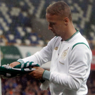 Charged: Leigh Griffiths ties a Celtic scarf to a goalpost