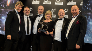 From left: Awards host John Bishop, Mark Howell from Flex-E-Rent, McCulla directors Brian Beattie, Carol Thompson and Ashley McCulla, and Steve Hobson, editor of Motor Transport