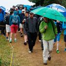 Fans shelter from the rain as they walk round the course during day one of The Open Championship 2017 at Royal Birkdale Golf Club, Southport.