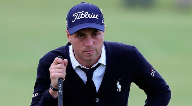 USA's Justin Thomas lines up a putt in his shirt, tie and cardigan on day one of the Open Championship