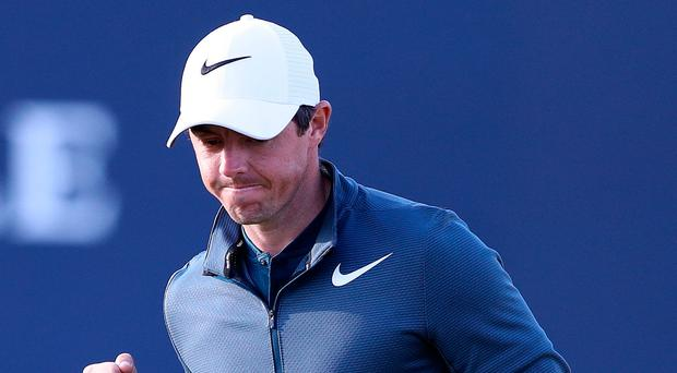 Fighting back: Rory gets back in contention with birdie putt on the 18th. Photo: Andrew Matthews/PA