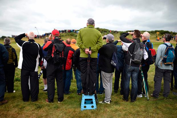 Spectators watch play on the 10th hole early on day two of the Open Golf Championship at Royal Birkdale golf course near Southport in north west England on July 21, 2017.
