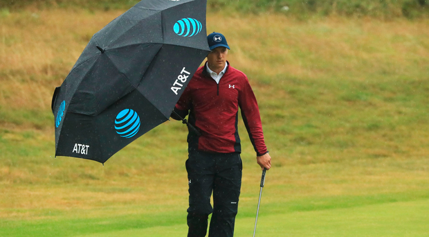 Got it covered: Jordan Spieth shields himself from the wind and rain but still impressed during his second round