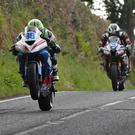 Right behind you: Derek McGee is pursued by Michael Dunlop yesterday