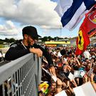 Write stuff: Lewis Hamilton delights the fans by signing autographs at the Hungaroring yesterday