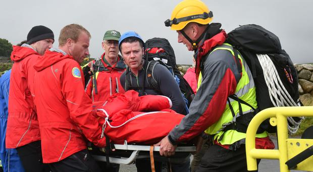 Emergency services bring the young climbers to safety yesterday