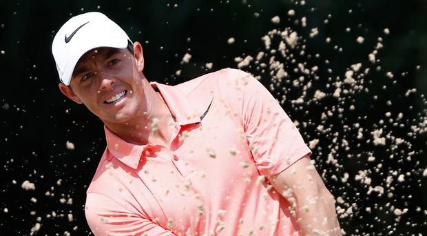 Escape route: Rory McIlroy plays out of a bunker on the fifth hole yesterday