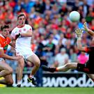 Tyrone's David Mulgrew scores his sides second goal despite Niall Grimley and goalkeeper Blaine Hughes of Armagh