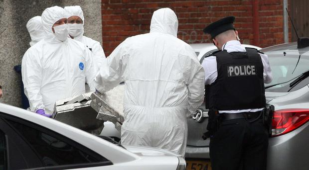 Police and forensic officers at the scene in Lurgan where a man's body was found