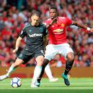 West Ham United's Javier Hernandez (left) and Manchester United's Paul Pogba battle for the ball during the Premier League match at Old Trafford, Manchester. Richard Sellers/PA Wire.