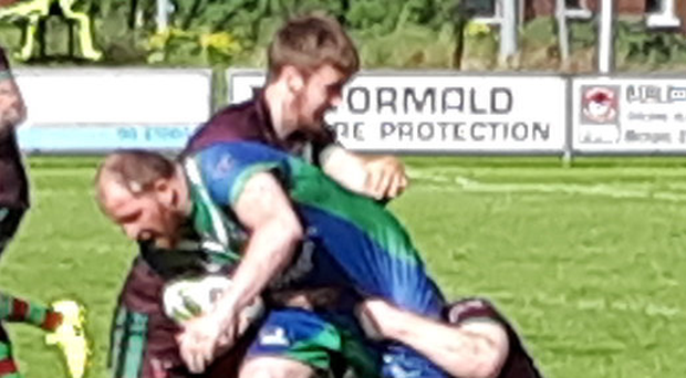 Tough game: Kenny McCombe is tackled by Andrew Coade