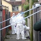 Forensics officers at the scene of the shooting