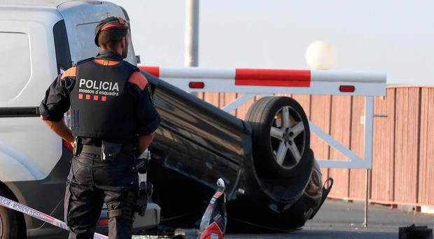 A policeman stands by a car involved in a terrorist attack in Cambrils, a city 120 kilometres south of Barcelona, on August 18, 2017. 'Alleged terrorists' drove into pedestrians in the Spanish seaside resort of Cambrils early August 18 before being shot dead by security forces, just hours after a similar attack in nearby Barcelona. / AFP PHOTO / LLUIS GENELLUIS GENE/AFP/Getty Images