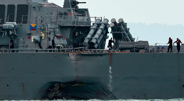 The guided-missile destroyer USS John S. McCain is seen with a hole on its portside after a collision with an oil tanker outside Changi naval base in Singapore on August 21, 2017. Ten US sailors were missing and five injured after their destroyer collided with a tanker east of Singapore early on August 21, the second accident involving an American warship in two months. / AFP PHOTO / Roslan RAHMANROSLAN RAHMAN/AFP/Getty Images
