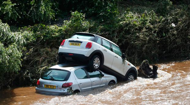 Cars washed into the river Faughan in Drumahoe, Londonderry, after heavy rain left a trail of destruction. Niall Carson/PA Wire