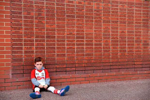 The beautiful game - football fans from around the world - A young Southampton fan next to a brick memorial wall before the Premier League match at St Mary's, Southampton.