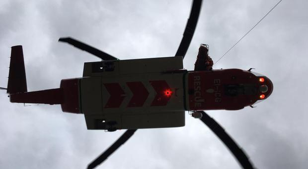 The Rescue 116 helicopter winching the injured woman to safety. Credit: Mourne Mountain Rescue Team