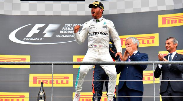 Jump to it: Lewis Hamilton celebrates on the podium after winning the Belgian Grand Prix
