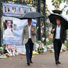 The Duke of Cambridge and Prince Harry depart after viewing tributes to Diana, Princess of Wales attached to the Golden Gates of Kensington Palace. Kirsty Wigglesworth/PA Wire