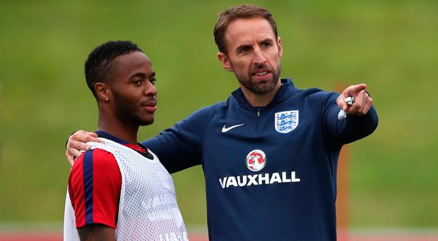 Whistle stop: England boss Gareth Southgate talks to Raheem Sterling in training yesterday. Photo: Nick Potts/PA