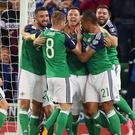 World beaters: Jonny Evans is mobbed by his Northern Ireland team-mates after scoring at Windsor Park last night