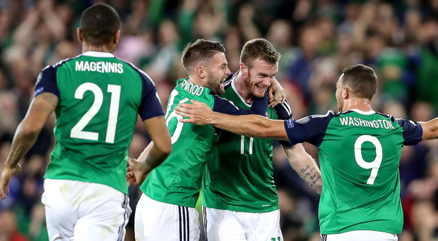 As one: Josh Magennis, Oliver Norwood and Conor Washington rush to congratulate Chris Brunt after his free-kick against the Czech Republic