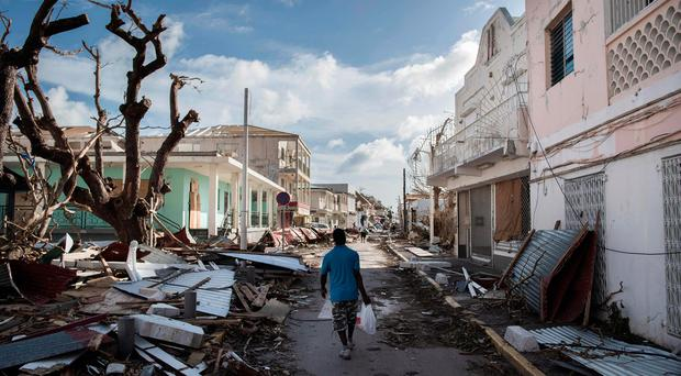 A man walks on a street covered in debris after hurricane Irma hurricane passed on the French island of Saint-Martin, near Marigot on September 8, 201 AFP PHOTO / Martin BUREAUMARTIN BUREAU/AFP/Getty Images