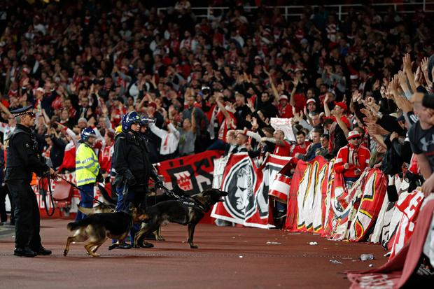 Police inside the stadium keep an eye on Cologne supporters in the stands as the kick off is delayed due to crowd safety issues ahead of the UEFA Europa League Group H football match between Arsenal and FC Cologne at The Emirates Stadium in London on Sept
