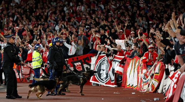 Police inside the stadium keep an eye on Cologne supporters in the stands as the kick off is delayed due to crowd safety issues ahead of the UEFA Europa League Group H football match between Arsenal and FC Cologne at The Emirates Stadium in London on September 14, 2017. Kick-off in the Europa League match between Arsenal and Cologne at the Emirates Stadium in London on Thursday has been delayed by an hour in the interests of crowd safety, the Premier League club announced. / AFP PHOTO / Adrian DENNISADRIAN DENNIS/AFP/Getty Images