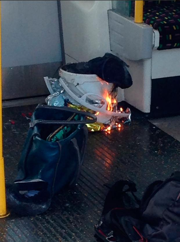 An image taken from a user generated content uploaded on social networks on September 15, 2017, shows a white container burning inside a London Underground tube carriage. Police and ambulance services said they were responding to an