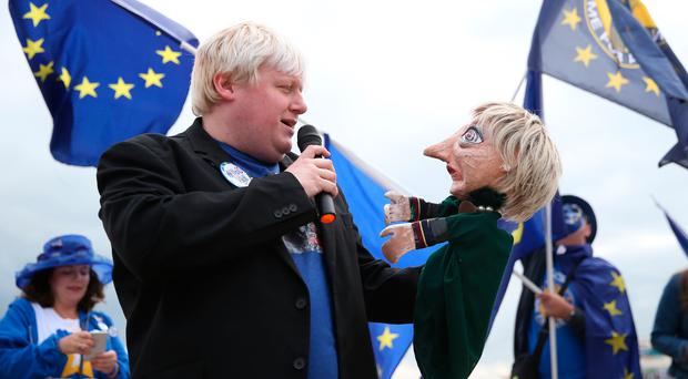 A Boris Johnson impersonator holds a Theresa May puppet during an Exit for Brexit rally during the second day of the Liberal Democrats Autumn Conference at the Bournemouth International Centre