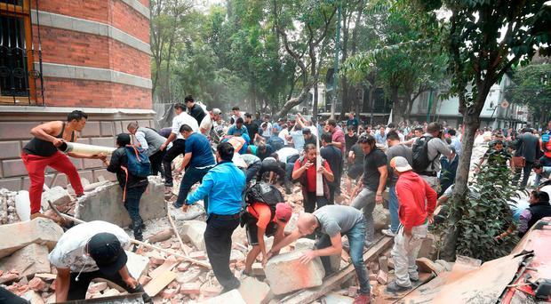 People remove debris of a damaged building after a quake rattled Mexico City