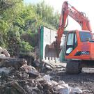 Work to remove a three-metre high security wall that divides Springfield Road and Springhill Avenue in west Belfast.