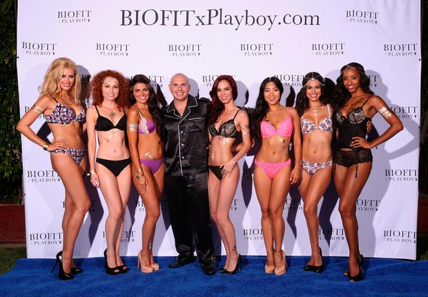 FILE - SEPTEMBER 27: Playboy magazine founder Hugh Hefner passed away on September 27 at the Playboy Mansion. He was 91 years old. HOLMBY HILLS, CA - AUGUST 16: Playboy brand partner Pitbull (C) poses with Playmates (L-R) Kennedy Summers, Scarlett Keegan, Val Keil, Jaime Edmondson, Hiromi Oshima, Raquel Pomplun and Neferteri Shepherd for the reveal of BIOFITxPlayboy during the Annual Midsummer Night's Dream Party at the Playboy Mansion hosted by Hugh Hefner on August 16, 2014 in Holmby Hills, California. (Photo by Christopher Polk/Getty Images for Playboy)