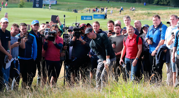 Fan-tastic: Rory McIlroy plays from the rough on the 17th at the British Masters at Close House yesterday after a fan found his ball