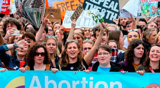 Protesters hold up placards as they take part in the March for Choice in Dublin on Saturday afternoon