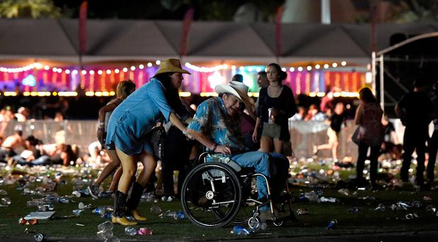 A man in a wheelchair is taken away from the Route 91 Harvest country music festival after apparent gun fire was heard on October 1, 2017 in Las Vegas, Nevada. There are reports of an active shooter around the Mandalay Bay Resort and Casino. (Photo by David Becker/Getty Images)