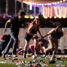 People run from the Route 91 Harvest country music festival after apparent gun fire was hear on October 1, 2017 in Las Vegas, Nevada.