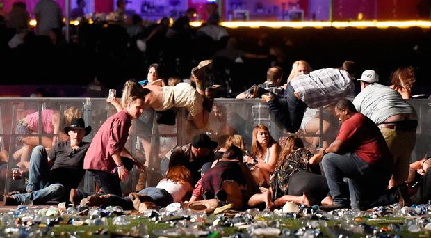 People scramble for shelter at the Route 91 Harvest country music festival October 1, 2017 in Las Vegas, Nevada.