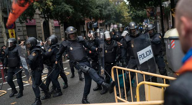 Spanish riot police removes fences thrown by people to them as they try to prevent people from reaching a voting site at a school assigned to be a polling station by the Catalan government in Barcelona, Spain, Sunday, 1 Oct. 2017. (AP Photo/Felipe Dana)