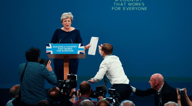 A protester gives a piece of paper written as a mock P45 to Britain's Prime Minister Theresa May. Pic: / AFP PHOTO / PAUL ELLISPAUL ELLIS/AFP/Getty Images