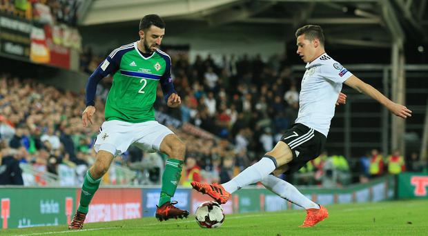 Northern Ireland's Conor McLaughlin jinks past Germany's Julian Draxler. Photo by David Maginnis/Pacemaker Press