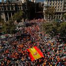 People carry a Spanish flag during a march in downtown Barcelona, Spain, to protest the Catalan government's push for secession from the rest of the country yesterday