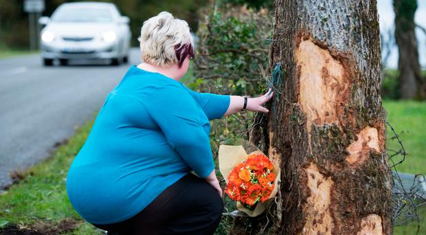 A friend leaves flowers near the scene of the accident which claimed the life of Natasha Carruthers