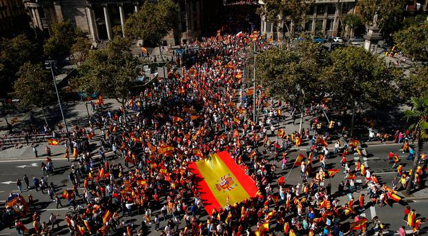 People carry a Spanish flag during a march in downtown Barcelona, Spain, to protest the Catalan government's push for secession from the rest of the country