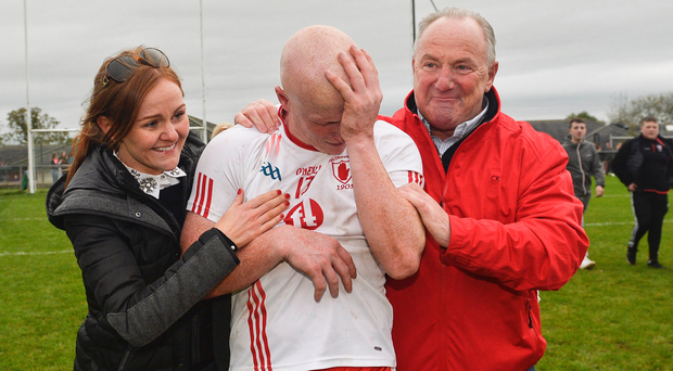 Emotional: Lamh Dhearg's Paddy Cunningham is congratulated by his wife Claire and his father Paddy after winning the Antrim Football final at his sixth attempt